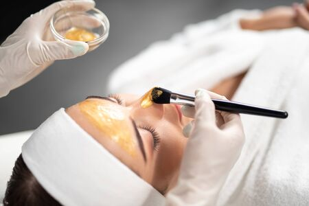 Beautician applying gold cosmetic mask on woman face Imagens