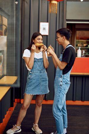 Asian guy and lady eating sweet corn outdoor