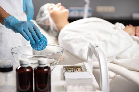 Beautician in sterile gloves soaking sponge in cleansing liquid Stockfoto