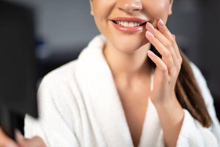 Junge Frau mit schönem Lächeln, die ihren Mundwinkel berührt Standard-Bild