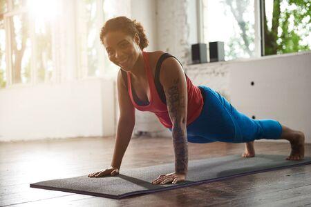 Pretty smiling woman doing plank in gym Zdjęcie Seryjne