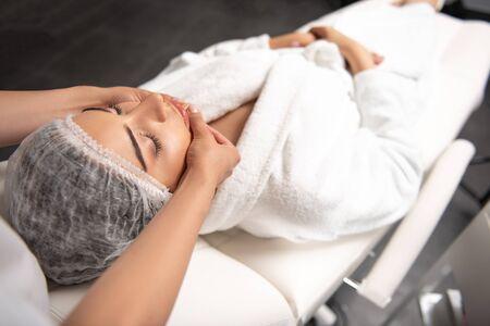 Professional masseuse massaging lady face at spa salon Stock Photo