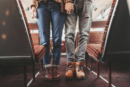 Love is in the air. Waist down portrait of beloved hipster man and woman holding hands while staying together in retro bus cafe