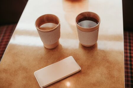 Close up top angle picture of two cup with hot beverage staying on table and mobile phone beside