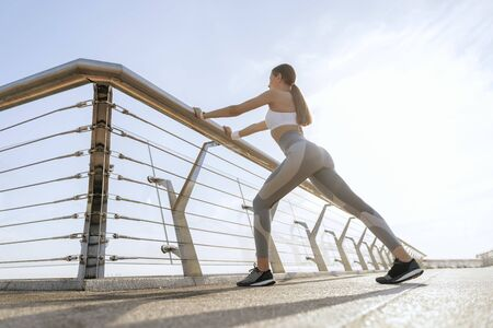 Young athletic lady doing leg lunge exercise