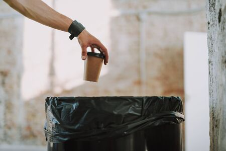 Hand with carton cup of coffee above the rubbish bin 写真素材 - 128543080