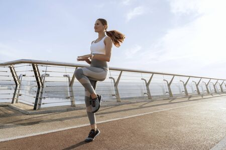 Young lady doing jog in place on foot bridge