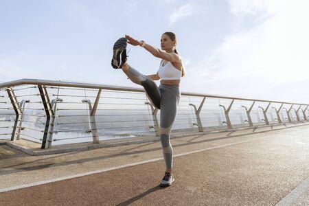 Young lady doing leg swing on foot bridge Stock Photo