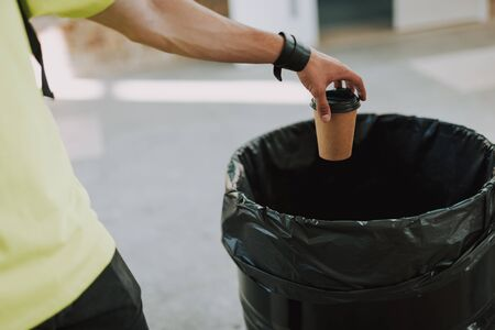Man throwing paper cup into rubbish bin