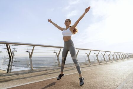 Sportive happy lady jumping up on foot bridge