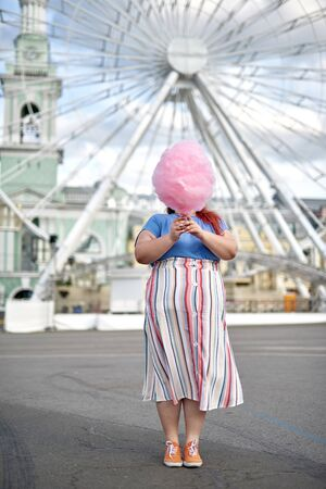 Young and fat woman holding cotton candy covering face