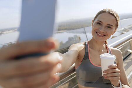 Happy sportive lady making selfie on foot bridge