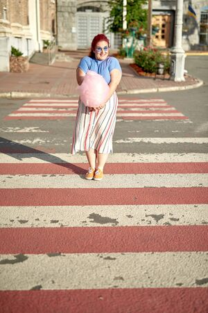 Young fat woman on crosswalk with cotton candy 版權商用圖片