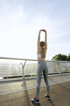 Sportive young lady on morning training on bridge