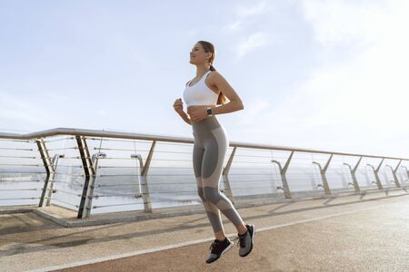 Sportive lady doing run in place on foot bridge