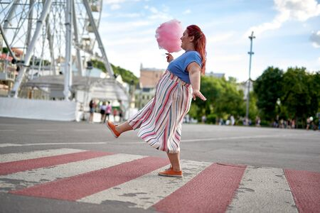 Young fat woman walking on city crosswalk with cotton candy 版權商用圖片