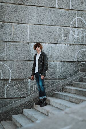 Calm young rocker on stone stairs standing alone