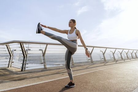 Sportive lady doing leg swing on foot bridge