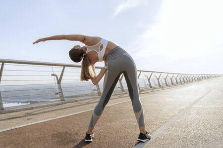 Slender athletic lady doing side body bending