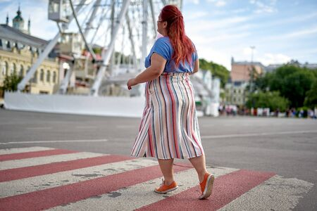 Fat young woman walking on city crosswalk