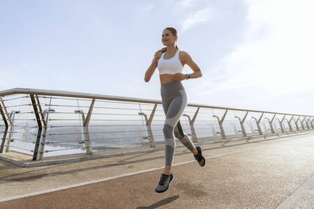 Happy lady doing run in place training outdoor 写真素材