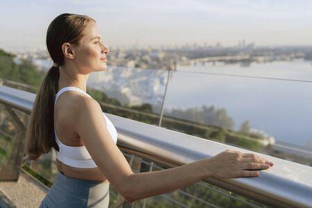 Relaxed sportive lady meet sunrise on foot bridge