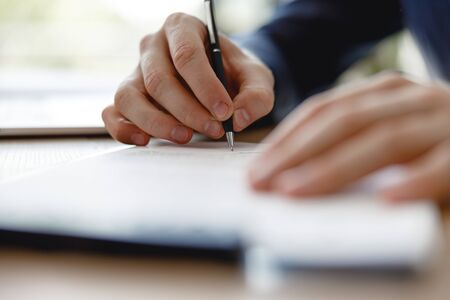 Black pen in the hand of man signing documents