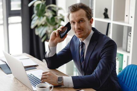 Confident businessman with his smartphone and laptop