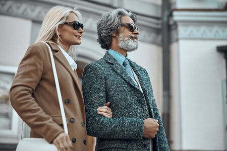 Mature couple in coats and sunglasses stock photo