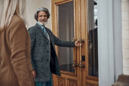 Gentleman opening the door for lady stock photo