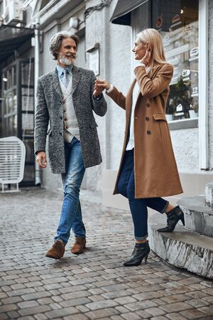 Helpful gentleman giving hand to lady stock photo 版權商用圖片
