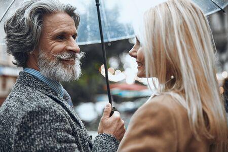 Mature couple standing under one umbrella stock photo