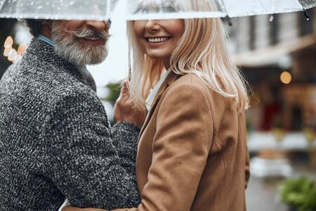Smiling couple under one umbrella together stock photo Imagens - 128762565