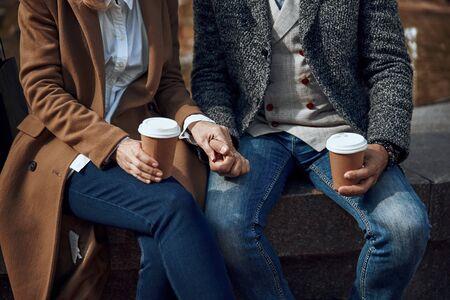 Loving couple with coffee holding hands stock photo 版權商用圖片