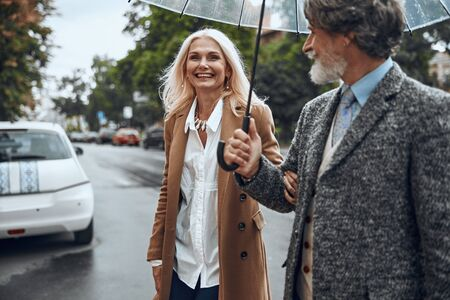 Happy woman holding man under arm stock photo