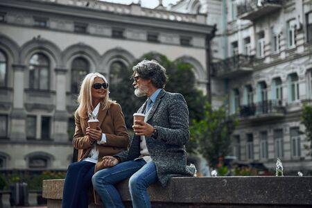 Two friendly people enjoying coffee outdoors stock photo