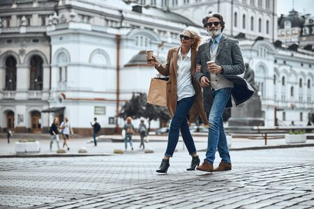 Happy couple walking and enjoying coffee stock photo 版權商用圖片 - 128763901