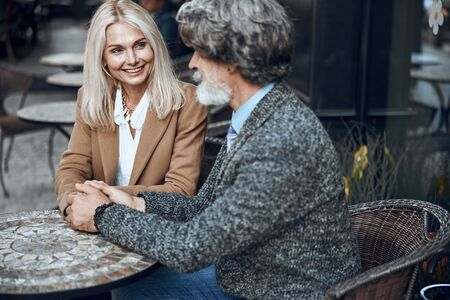 Loving couple holding hands in cafe stock photo