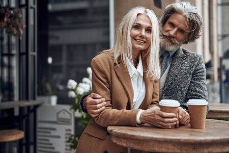 Smiling couple embracing at the cafe high table stock photo