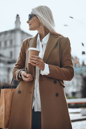Smiling lady with coffee outdoors stock photo