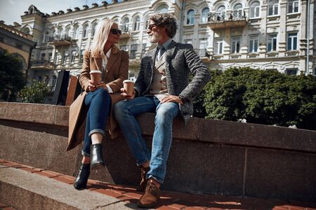 Friendly couple sitting with coffee outdoors stock photo 版權商用圖片