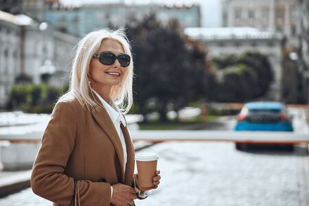 Mirthful woman with carton cup of coffee stock photo