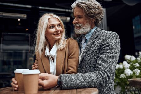 Happy mature couple with coffee in street cafe stock photo