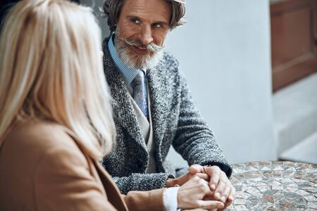 Smiling bearded man touching hands of woman stock photo