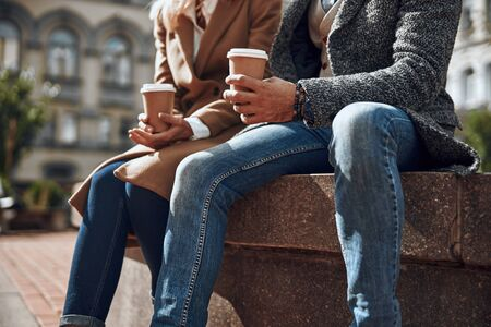 Couple in jeans sitting with cups of coffee stock photo 版權商用圖片 - 128764432