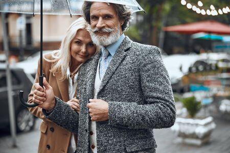 Cheerful adult couple under umbrella stock photo
