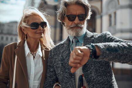 Adult man and woman looking at the watch stock photo