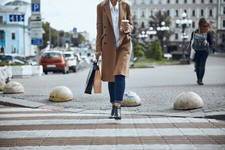 Woman in coat crossing the road stock photo