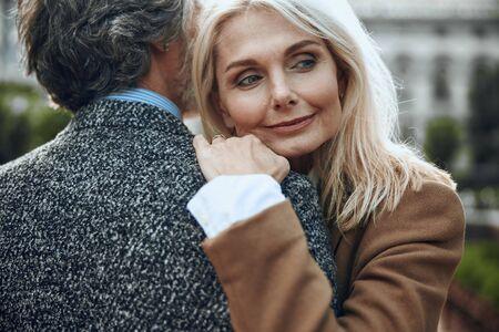 Peaceful woman hugging shoulder of man stock photo
