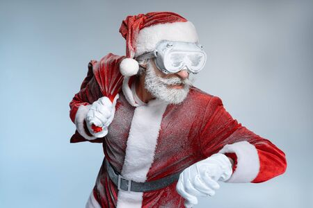 Santa Claus looking at watch holding sack with presents Stock Photo